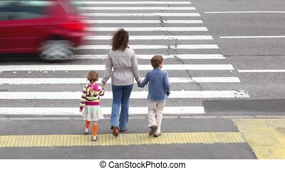Mother and children, cross road at pedestrian crossing,...