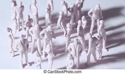 Group of little unpainted toy men and women stand and drop shadows