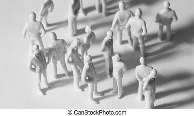 Group of little unpainted toy people stand and drop shadows,...