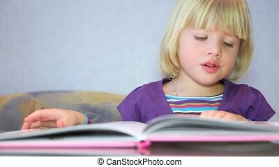 Little girl read a picture-book and something tells