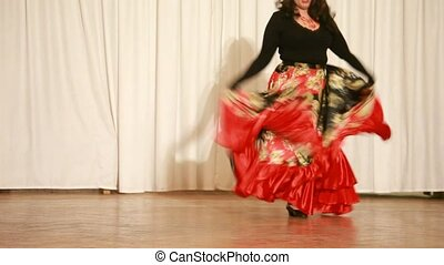 Gypsy female in red dress perform traditional dance