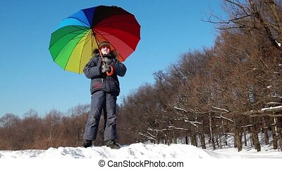 Boy stand and hold parasol over his head - Boy in winter...