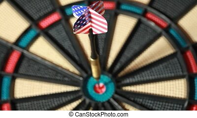 Metalic arrow hit the center of dartboard, closeup view