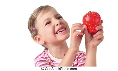 Girl holding timer in the form of strawberries, she regards...