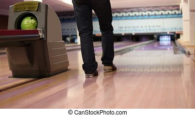 Man throw ball and hit pins in bowling club, parquet floor...