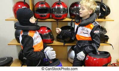 Two boys choose to helmets for on go-cart racings, indoor