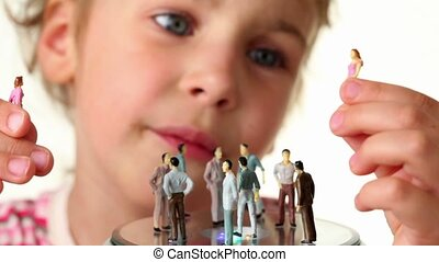 Girl holds toy figurines of women, in front of her placed spinning toy podium