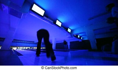 People play bowling in dark, illuminated with blue light,...