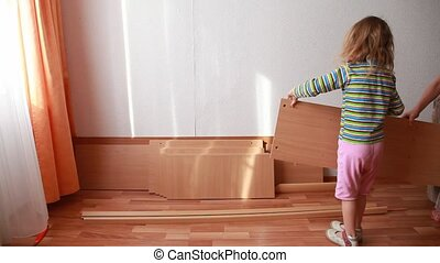 Two little kids place wooden boards in bright room