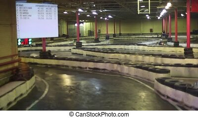 Carting race is in indoor place with video board - Carting...