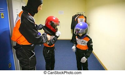 father prepares two boys for go-cart racing. - Young father...