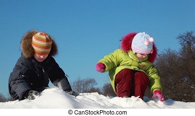 kids enjoy play snowballs, girl chuck snow to boys face and...