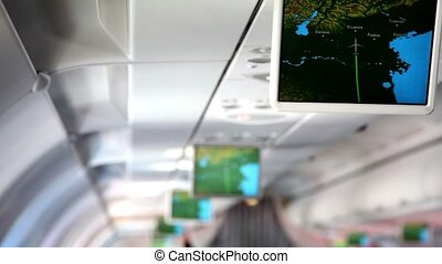 Aircraft cabin, under ceiling hung displays and show...