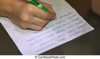 Hand of boy which writes the text on a sheet of paper