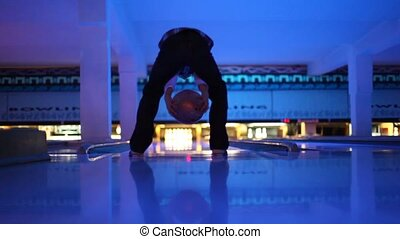 Boy throws ball in illuminated bowling club, the rear view