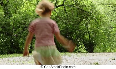 Girl hopping and runs away across meadow all strewn fluff,...