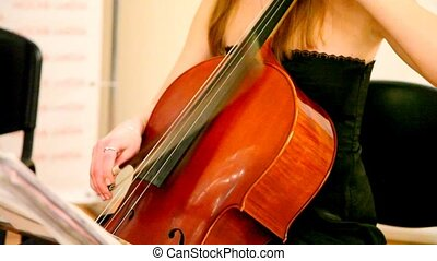 Close-up of woman plays a violoncello - Close-up of young...