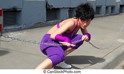 Woman make dance performance with chain, at pavement