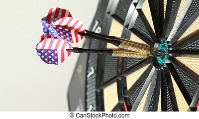 Three metallic darts hit special playboard, closeup, side...
