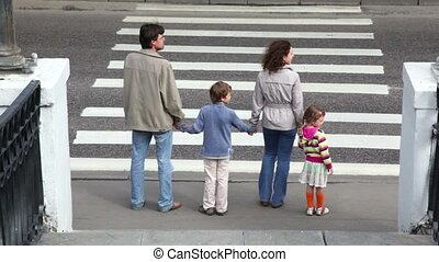 Family stand at the edge of pedestrian crossing road, parents keep childrens hands