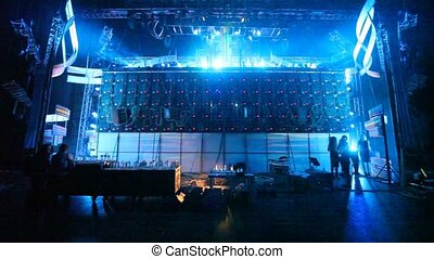People work behind equipment illuminated offstage