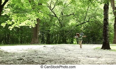 Boy runs closer across forest meadow all strewn fluff - Boy...