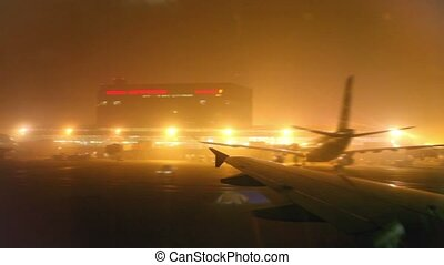 Aircraft landed at airport at night, view from porthole