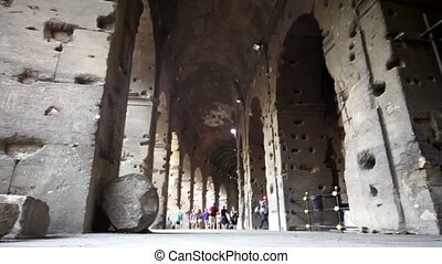 Colosseum corridor inside, tourists walk along, camera near...