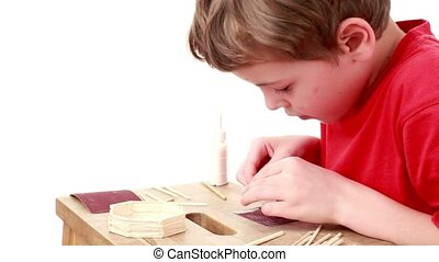 Boy whet match using sandpaper which lies on table for this,...