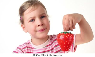 Girl holding timer in the form of strawberries, she points...