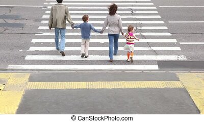 Parents and kids cross road by pedestrian crossing, after car passed