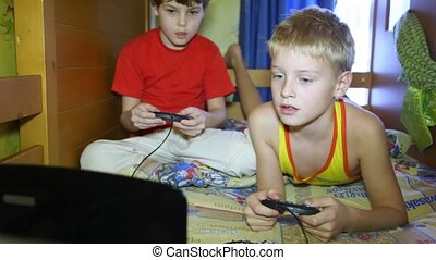 Two boys sit and play a computer game - Two boys play a...