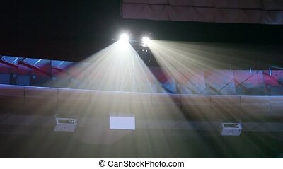 Two projectors shine white light under ceiling in darkness