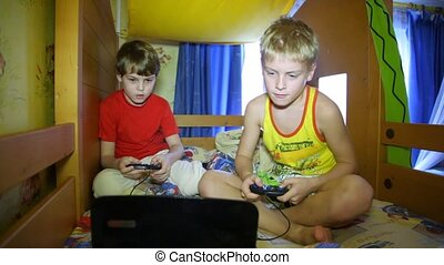 Two boys play a computer game with joysticks in hands