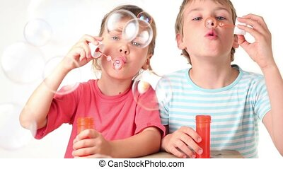 Two kids boy blows soap bubbles and try to catch them