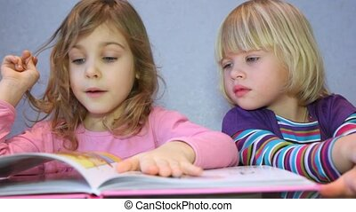 Two little girls read a picture-book