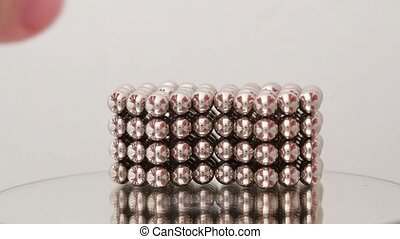 Hands take magnet balls structure and divide it, then put...