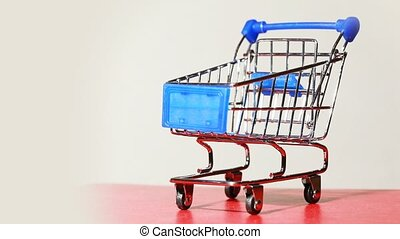 Little metallic shopping cart turning around on platform,...