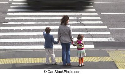 Mother and children, cross road at pedestrian crossing after...