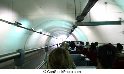 People riding on bus roof through tunnel in city center -...