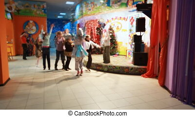 little children having fun with artificial snow in building