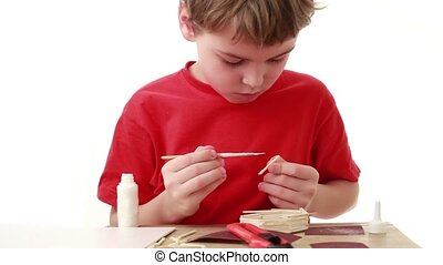 Boy put adhesive to match, in front of him on table unfinished house from matches