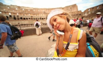 Girl stay in coliseum with cell phone near ear, then show...