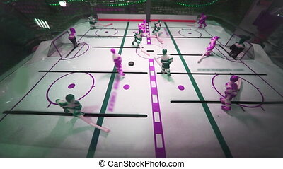 play in toy table hockey game at supermarket, nonreal...