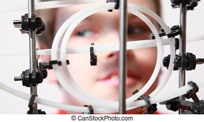Boy looks at marbles go through 360 degree loop, closeup...