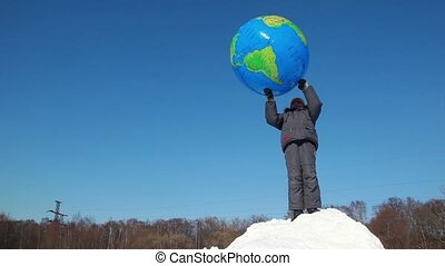 Boy stand on snow pile and hold inflated ball over head,...