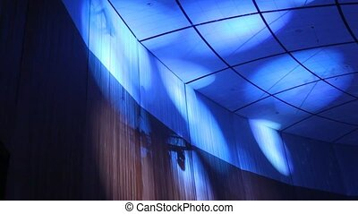 Blue light of projectors moves on ceiling in darkness