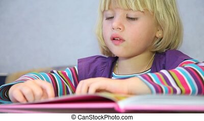 Close-up of little girl considers pictures in book