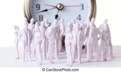 Little colorless toy men and women stand in front of big clock