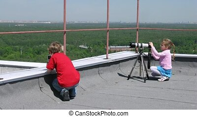 Kids play with digital cameras on top of the roof